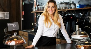 cheerful waitress standing behind the bar